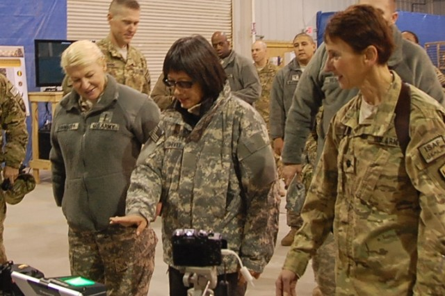 Heidi Shyu, acting assistant secretary of the Army for Acquisition, Logistics and Technology, holds her hand over a guardian system used to capture fingerprints which will be stored in an interoperable system to assist in providing positive identification of personnel. The guardian system is part of a biometric automated toolset that captures several types of biometric information. Gen. Ann E. Dunwoody, commanding general, Army Materiel Command, is watching while Lt. Col. Joanne T.  Farris, biometrics program manager explains the capabilities of the toolset.