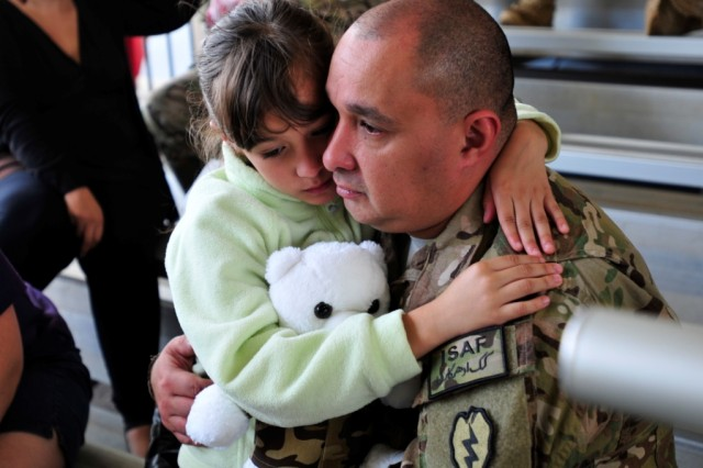 Staff Sgt. Julio Riveraperez, C Company, 3rd Battalion, 25th Aviation Regiment, 25th Combat Aviation Brigade, holds his daughter Jan. 4 on Wheeler Army Airfield, Hawaii, before deploying to Afghanistan in support of Operation Enduring Freedom.