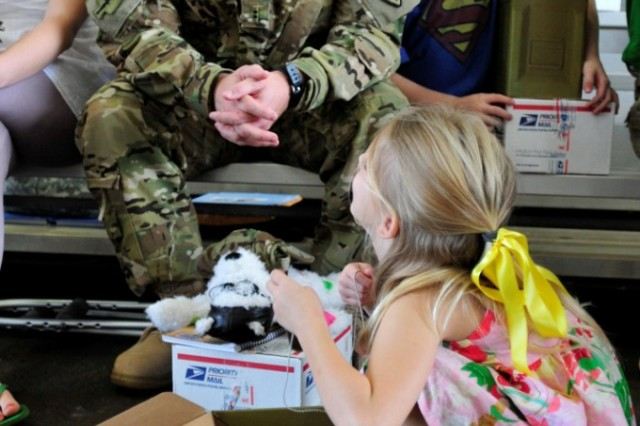 Chief Warrant Officer 2 Charles Basham, D Company, 3rd Battalion, 25th Aviation Regiment, 25th Combat Aviation Brigade, watches his daughter open a care package Jan. 4 before deploying to Afghanistan in support of Operation Enduring Freedom on Wheeler Army Airfield, Hawaii.