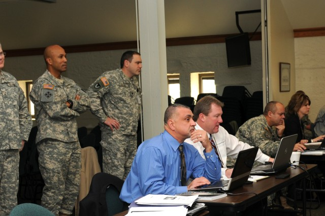 Army Sustainment Command senior leaders Brig. Gen. Brian Layer (center left) and Col. Victor Harmon (center right) stand with LOGSA representative Brian Brown (left) to observe Decision Support Tool training Jan. 4 at Rock Island Arsenal, Ill.