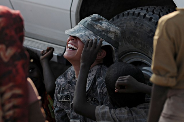 "KARABTI SAN, Djibouti -- U.S. Army Specialist Tiffany Larriba, Civil Affairs Team 4902, 490th Civil Affairs Battalion team member, laughs as her hat is pulled over her eyes by a local boy at Karabti San, Djibouti, January 3, 2012. Larriba spends the day interacting and playing with the children, and teaches them basic English in the evenings as part of the ""Soldier in the Classroom"" program."