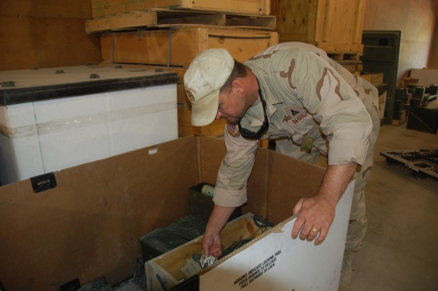 Matthew Hawver, quality assurance specialist (ammunition surveillance), checks through a box of items turned in at various ammunition amnesty boxes at the Bagram Airfield, Afghanistan, ammunition supply point. Amnesty ammunition is checked and when determined safe to use it can be issued to Soldiers.