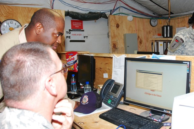 Ricky L. Gant, CECOM IT logistics assistance representative from Fort Bliss, Texas, works with Master Sgt. James A. Carter, the maintenance management noncommissioned officer-in-charge, 298th Combat Sustainment Support Battalion, a Mississippi National Guard unit, in checking data on the SAMS II database which tracks everything maintenance related from for the unit.