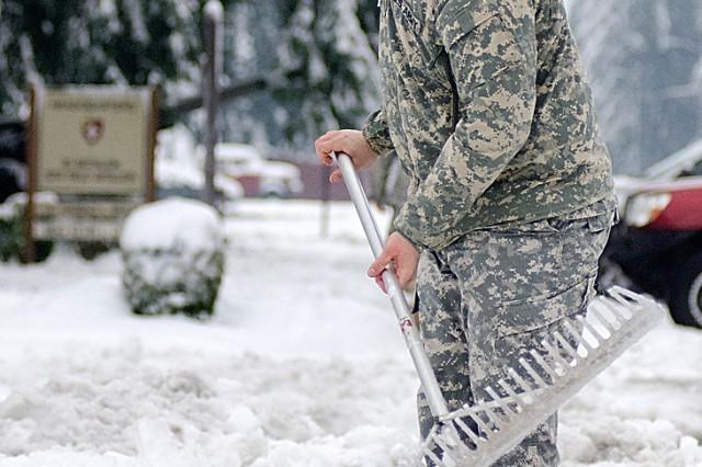 A JBLM Soldier clears a main walk.