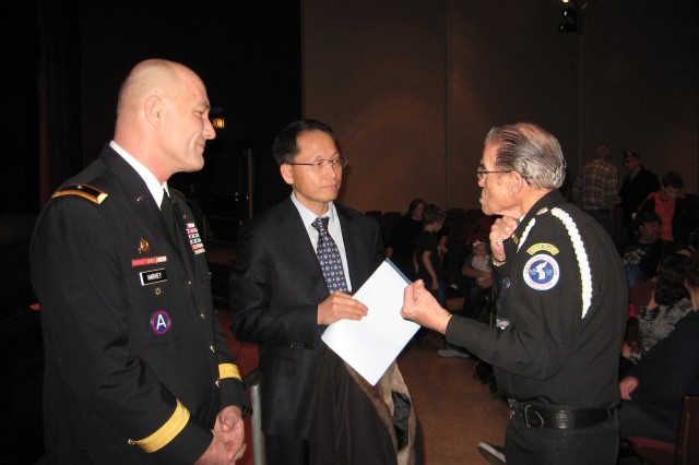 Brig. Gen. Thomas Harvey (left), ASC deputy commanding general for operations,  speaks with Heechan Woo (center), Korean consulate, and Jerry Guinn (right), ceremony organizer, prior to the presentation of the Korean Ambassador Peace Medals in Moline, Ill.