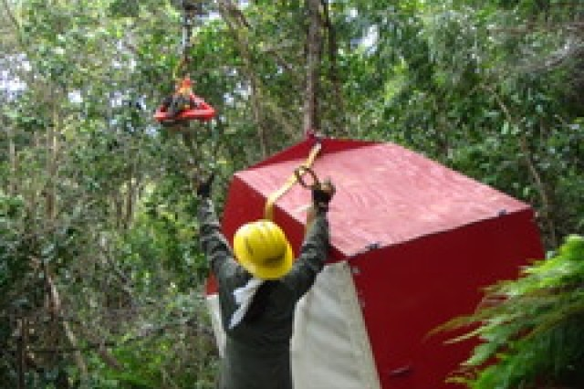 Due to the remote locations of many of the sites, the Oahu Natural Resource Team must use helicopters to sling-load plants to be outplanted. In this picture a helicopter delivers a box filled with eight endangered plants to a remote native forest where the NRT staff will re-introduce them to the wild.