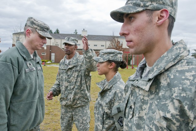 Sergeant 1st Class Shvoda Gregory (center), motor sergeant for the 557th Engineer Company, 864th Engineer Battalion, walks Sgt. David Clark (far left), an administrations officer with Headquarters, Headquarters Company, 864th Eng. Bn., through the process of inspecting a squad of Soldiers in formation Jan. 24 outside the battalion's headquarters on Joint Base Lewis-McChord, Wash. The instruction was part of a five-day junior leadership development course the battalion administers quarterly to better prepare its new and future leaders.