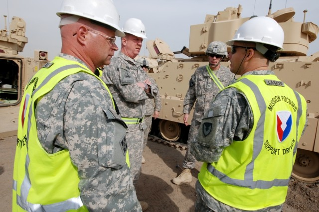 Lt. Col. Kenneth Gill (left to right in hard hats), Army Field Support Battalion-Kuwait commander, Maj. Gen. Kenneth S. Dowd, 1st Theater Sustainment Command commander, and Col. John S. Laskodi, 402nd Army Field Support Brigade commander, talk with Col. Scott Efflandt, 1st Brigade Combat Team, 1st Cavalry Division commander, Jan. 18, 2012, at Camp Arifjan, Kuwait. Army Field Support Battalion-Kuwait, 402nd Army Field Support Brigade, began issuing heavy brigade combat team equipment to the Ironhorse Brigade Jan. 3.