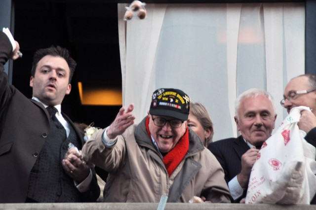 World War II veteran Lt. Everett G. Andrews throws nuts off the balcony of City Hall in Bastogne, Belgium, to commemorate the 67th anniversary of the Battle of the Bulge.