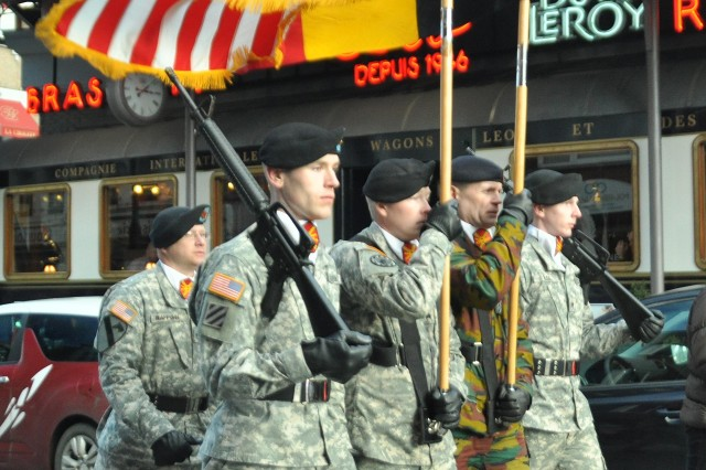 American and Belgium Army color guards lead the parade in Bastogne, Belgium.