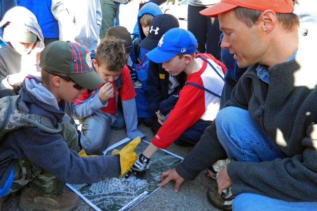 "CAMP BULLIS, Texas "" Bryan Hummel, a natural resources technician from 502nd Air Base Wing's Civil Engineering Squadron, points out exact map locations for a volunteer conservation project to Cub Scouts and parents of Pack 500 here Jan. 21."