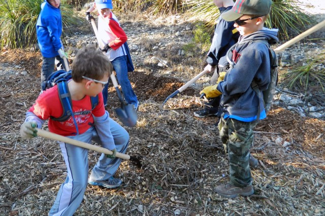 "CAMP BULLIS, Texas "" Cub Scouts of Pack 500 use rakes and shovels to spread mulch and prevent erosion during a volunteer conservation project here Jan. 21."
