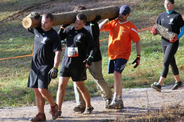 Pete DeMattei (left) and Blake Burd (right) carry a log up and down a hill with teammates during one of the 25 obstacles on the course.