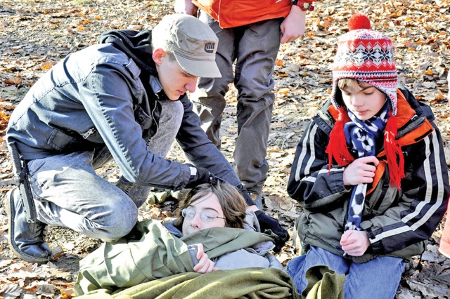 Eagle Scout Ben Barnhart helps make Tristen Mann comfortable during a first aid exercise at Wiesbaden's Klondike Derby, in Wiesbaden, Germany.
