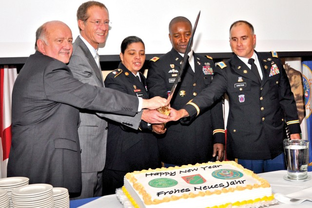 Wolfgang Nickel (from left), Wiesbaden City Parliament chairman; Axel Wintermeyer, chief of the Hessian State Chancellery; 5th Signal Command Sgt. Maj. Marilyn Washington; Col. Bruce Crawford, commander of 5th Signal Command; and Col. David Carstens, U.S. Army Garrison Wiesbaden commander, cut the ceremonial cake during the New Year's Reception.