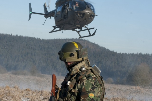 A Bulgarian soldier watches a U.S. medical evacuation UH-72 Lakota helicopter prepare to land during Operational Mentor Liaison Team training at the Joint Multinational Readiness Center (JMRC) in Hohenfels, Germany, Jan. 18, 2012. JMRC conducts several OMLT rotations each year, training multinational partners to ensure they are prepared for deployment to Afghanistan with the ability to train, advise and enable the Afghan National Army while possessing the skills to survive on the battlefield. (U.S. Army photo by Spc. Ashley Webster/Released)