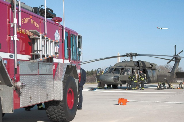 Members of the Fort Myer Fire Department gather around a Black Hawk helicopter after training with the Arlington Fire Department and personnel from the Pentagon.