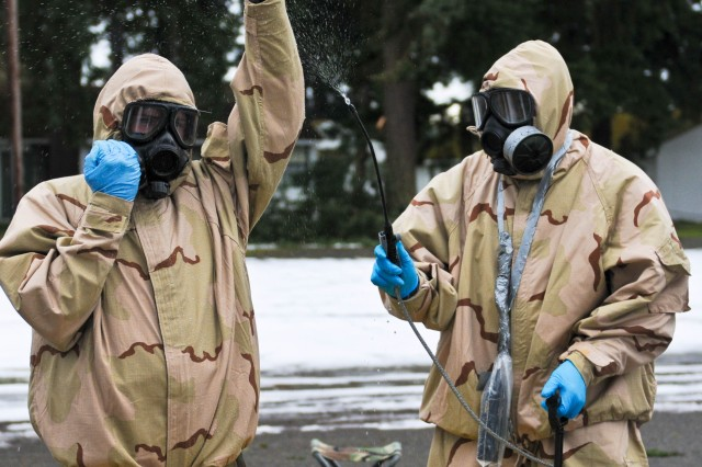 "JOINT BASE LEWIS-McCHORD, Wash. ""-Soldiers of Bravo Company, 110th Chemical Battalion (Technical Escort), start the decontamination process during an evaluated mission simulation at a training site on Joint Base Lewis- McChord, Wash., Jan 24."