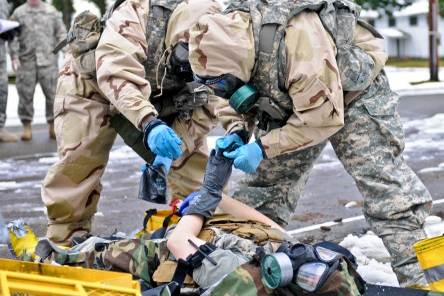 "JOINT BASE LEWIS-McCHORD, Wash. ""-Staff Sgt. Oladapo A. Ogungbayi, left, decontamination team leader, and Staff Sgt. Jacob V. Wooden, right, trans-load team leader, carefully take the gloves off of explosive ordnance disposal team leader Sgt. Didrich L. Maas, middle, after he was 'injured' during a mission simulation evaluating the proficiency of Bravo Company, 110th Chemical Battalion (Technical Escort), at a training site on Joint Base Lewis- McChord, Wash., Jan 24."