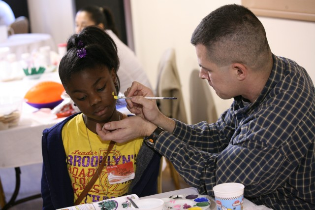 Lt. Col. Phil Speth, SMDC G3 office, paints the face of a child during the U.S. Army Space and Missile Defense Command/Army Forces Strategic Command's Winter Wonderland event at The Overlook on Redstone Arsenal for families through Survivor Outreach Services on Jan. 28.