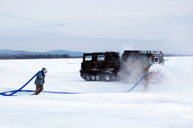 Soldiers from the 56th Engineer Company spread water to thicken a path of the Tanana River's frozen surface during an ice-bridge construction project Jan. 25, 2012, near Fort Wainwright, Alaska.