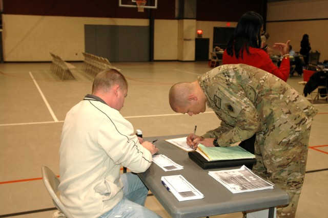 Cpl. Eric McNulty, an infantryman from Southern Plains, N.C., fills out the e-benefit form with military service coordinator Nathan Talley after returning from deployment with C Company 279th Infantry Regiment, 45th Infantry Brigade Combat Team.