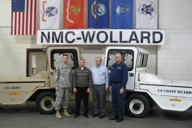 "JOINT VENTURE "" (left to right: Lt. Col. Steve Ansley, Product Manager for Aviation Ground Support Equipment (AGSE); Bruce Steingart, Vice President of NMC-Wollard; Timothy Keyes, President of NMC-Wollard; and Chief Warrant Officer Greg McDermott, Support Equipment Chief of the U.S. Coast Guard Aviation Logistics Center) Team members of the Standard Aircraft Towing System (SATS) Joint Venture pose in front of two SATS vehicles after the roll-off ceremony Feb. 1 at the NMC-Wollard Facility in Eau Claire, Wis. The SATS is a towing vehicle used for pushing or towing all Army rotary and fixed wing aircraft and now, the U.S. Coast Guard aviation assets. (Photo by PM AGSE)"