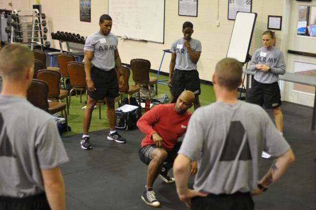 Chuck Carswell, an instructor from the CrossFit Decatur, Ga., branch, explains how to correctly do the front squat during a CrossFit certification at the Caro Fitness Center (CrossFit Fort Stewart), from Jan. 31 to Feb. 1, 2012.