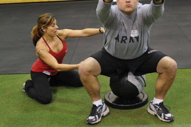 Sgt. Mathew Sovinski, a radar repairer assigned to Headquarters and Headquarters Company, 3rd Sustainment Brigade, receives a few pointers from CrossFit instructor Nicole Gordon, on how to do a proper squat. Soldiers from the 3rd Infantry Division participated in a two-day, Level 1 CrossFit certification at the Caro Fitness Center (CrossFit Fort Stewart) from Jan. 31 to Feb. 1, 2012.