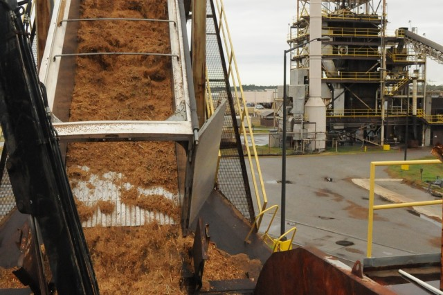 The chip vans are brought to the Central Energy Plan to unload the wood chips into the wood dump. The chips are then moved onto a conveyer system. The CEP in the back illustrates steam emission as it burns the wood chips. The CEP uses the chips to create steam, chilled water and hot water to over a hundred buildings on the installation.