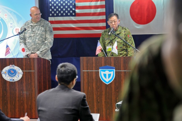 Col. Thomas Kunk, U.S. Army Pacific Contingency Command Post  G-3 and Col. Sumio Yamashita, Japanese Ground Self Defense Force (JGSDF) Middle Army G-3 discuss operations during a mock press conference at Camp Itami, Japan Feb. 2.   The press conference is part of Yama Sakura 61 which is being held just north of Osaka.  Yama Sakura is an annual, Japan-based, simulation-driven, joint-bilateral command post exercise held with JGSDF and U.S. forces.  Yama Sakura is designed to enhance U.S. and Japan combat readiness and interoperability and strengthen military relationships.