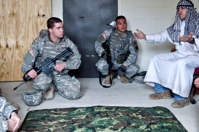 Captain Johnny Anderson (far left), Pfc. Joe N. Thieleman (center), and Sgt. 1st Robert J. Bentcliff, members of civil affairs team 81-12, A Company, 81st Civil Affairs Battalion, 85th Civil Affairs Brigade, talk to tribal leaders in a simulated key leader engagement during a situational training exercise at the Boaz Military Operation in an Urban Terrain site on Fort Hood Jan. 31.