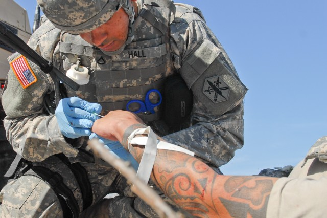 Unable to utilize veins in the tattooed arm of Staff Sgt. Rivera, Pvt. 1st Class Alexander Hall of 81st Civil Affairs Battalion, 85th Civil Affairs Brigade looks to the casualty's hand for a good vein during a simulated IED scenario Jan. 31 here at Fort Hood. Veins along the hands are often used as a secondary sight to provide Intravenous Fluids. (photo by Army Staff Sgt. Gregory Sanders, 85th CA BDE PAO)