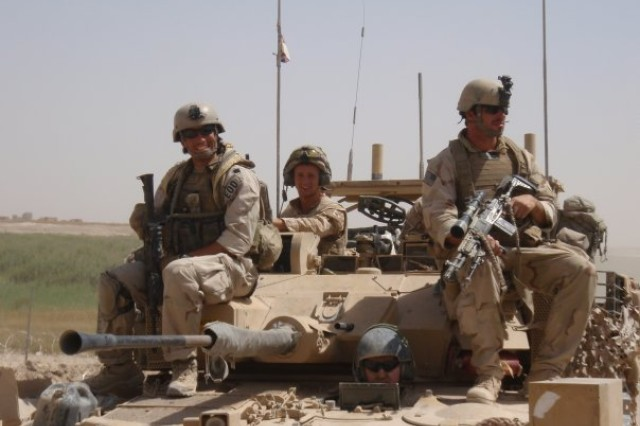 Staff Sgt. Shawn Hibbard, right, rides on a tank in Spin Majid, Helmand, Afghanistan, July 2009.