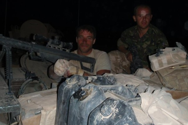 Following the 2009 fire fight in Afghanistan, Staff Sgt. Shawn Hibbard sureveys the damage on top of the British vehicle he used.