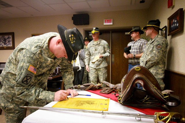 Lt. Col. Christopher Downey, commander of the 6th Squadron, 6th Cavalry Regiment, signs the official charter of the Order of the Mountain Cavalry, a professional organization made up of cavalry units within the 10th Mountain Division (LI), Jan. 27 at the Fort Drum Commons. (Photo by Capt. Michael Greenberger)