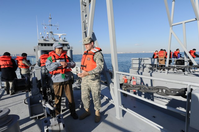 A Soldier assigned to the 481st Transportation Company gives a briefing about the Landing Craft Utility 2020 vessel to a member of the Tokyo Metropolitan Government during the exercise.