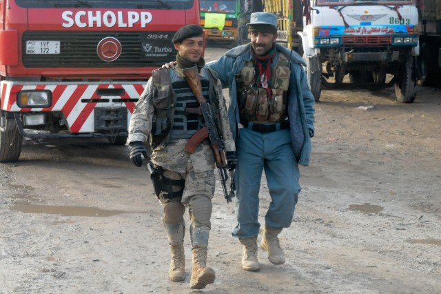 Two Afghan National Security Forces personnel walk side-by-side and share a light moment during a break from security operations just outside of Kandahar City, Afghanistan. Dubbed Operation Bald Knob, the Jan. 30, 2012, event was planned and led by Afghans.