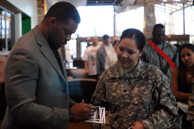 Heisman Trophy winner and former Dallas Cowboys running back Hershel Walker signs autographs for fans at Freedom Crossing Jan. 24, 2012. Walker was visiting members of Fort Bliss, Texas, to spread the message of seeking help if you have behavioral health issues.