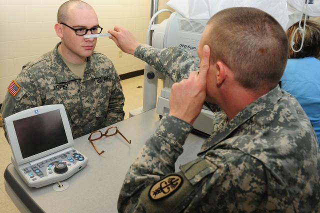 Pvt. Michael Lopez tries on a pair of the new 5As for Sgt. Brant Fechter at the 43rd Adjutant General (Reception) Battalion Optometry Clinic on Fort Leonard Wood, Mo., Jan. 31, 2012.