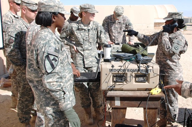 Staff Sgt. Kymberlee Clark (right), 2nd Platoon, 233rd Transportation Company, 113th Sustainment Brigade, makes a point while learning to set up VSAT communications during Redistribution Property Assistance Team Academy training Jan. 24, 2012, at Camp Virginia, Kuwait.
