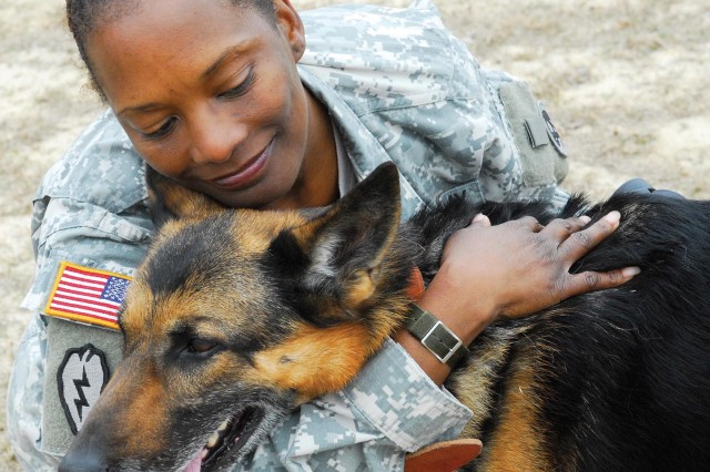 Staff Sgt. Alexis Scott hugs Arka on Friday at the Fort Benning kennel. The 8-year-old German shepherd is set to be retired from duty with the 209th Military Police Detachment later this year. Scott, who's assigned to the Warrior Transition Battalion, has filed paperwork to adopt her.