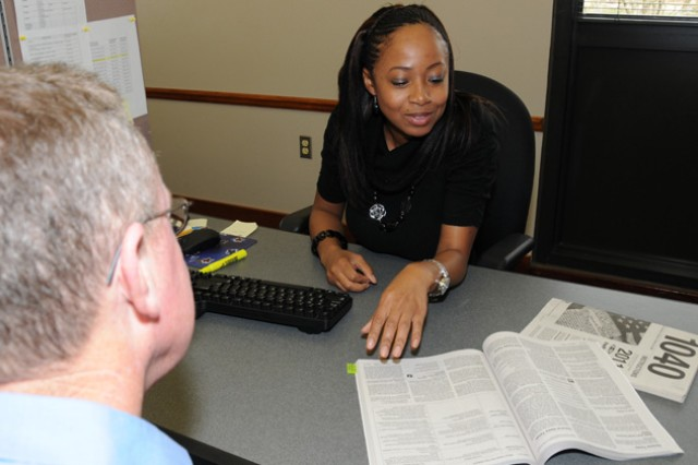 Sarah Apodaca, volunteer tax assistant at the Fort Rucker Tax Center, discusses a federal return with a client Feb. 6 shortly after the center opened for business to provide free tax advice, information, filing and e-filing services to active duty military, Family members and retirees.