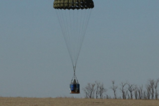A cargo chute floats a Container Delivery System bundle to the Southeast drop zone on Fort Sill, Okla., seconds after being dropped from a cargo plane.