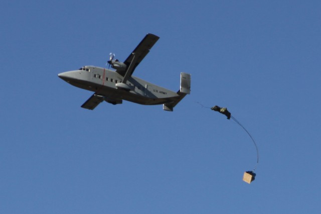 A 26-foot cargo chute begins to deploy from an airdrop pallet as it sails out the back of a C-23B+ Sherpa cargo plane 200 feet over the southeast drop zone on Fort Sill, Okla. The exercise simulated airdrops that the 168th BSB performs when dropping ammunition; meals, ready-to-eat; water and equipment to Soldiers in remote locations of Afghanistan, or emergency food and water packets to civilians in areas devastated by natural disasters.