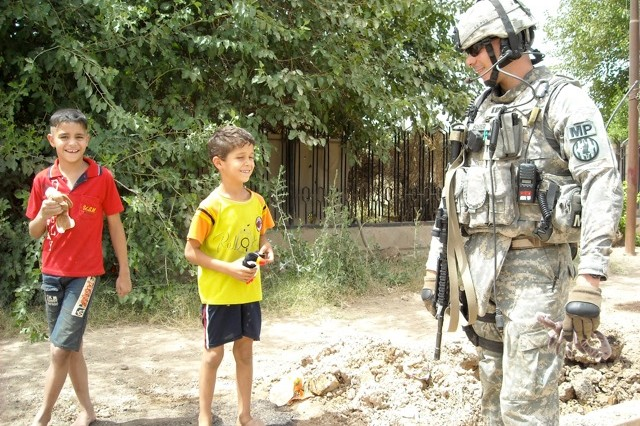 Capt. Adrian Foster hands out toys to local kids during a Police Transition Team dismounted patrol near the Khark local police directorate in Baghdad in March 2006.