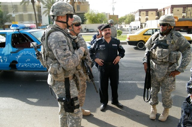 Capt. Adrian Foster conducts checkpoint inspections with members of the local Iraqi police force near Baghdad in March 2006.