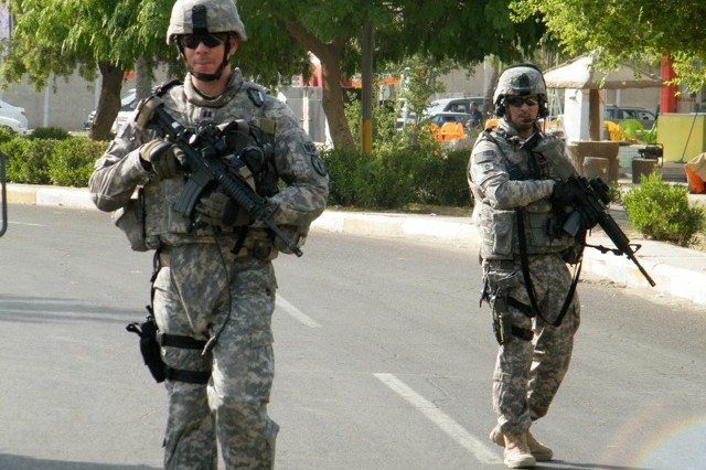 Capt. Adrian Foster and Sgt. 1st Class Ralph Saorrono conduct a dismounted patrol near Baghdad to detect/deter insurgent activity in concert withlocal Iraqi police in March 2006.