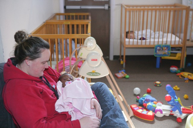 FORT SILL, Okla. -- Katie Parrish, an Armed Services YMCA employee, holds Jade Shepherd during afternoon nap time Feb. 6, 2012 at the facility in Lawton. ASYMCA uses grant money it receives from the Patriot Spouses Club to augment its food basket program.