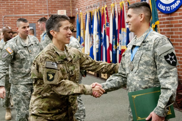Command Sgt. Major Dawn Rippelmeyer, 42nd Military Police Brigade command sergeant major, congratulates Staff Sgt. Hector Valadez, 4th Stryker Brigade Combat Team 2nd Infantry Division, for being inducted in the Sergeant Audie Murphy Club following a ceremony at the NCO Academy auditorium, Jan. 6. Four NCO's were inducted into the prestigious club during the ceremony.